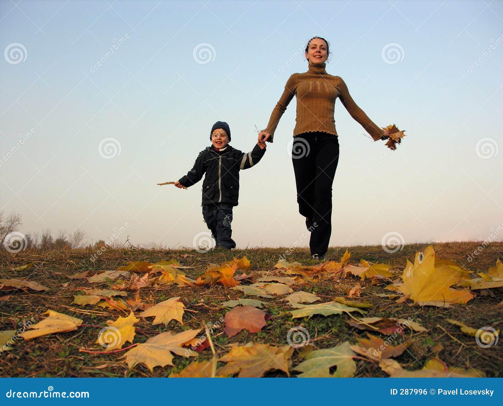 Lopende moeder met zoon op de herfstbladeren