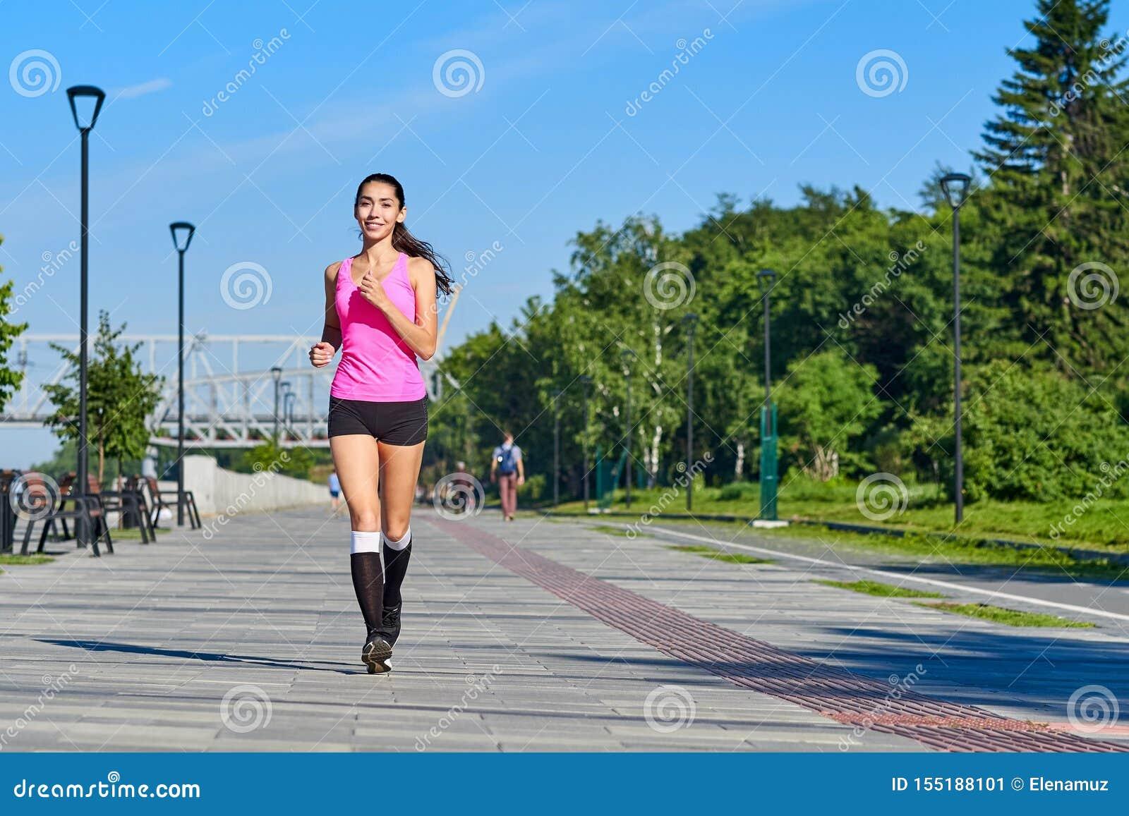 Lopende vrouw op de waterkant Ochtendjogging De atletentreinen