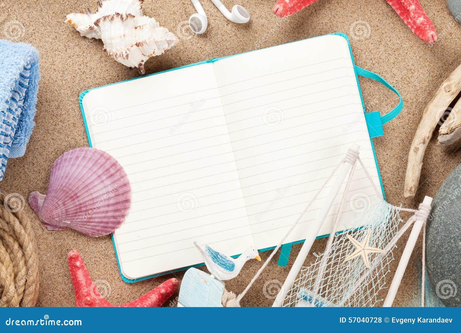 Lopp och semesternotepad med objekt över sand