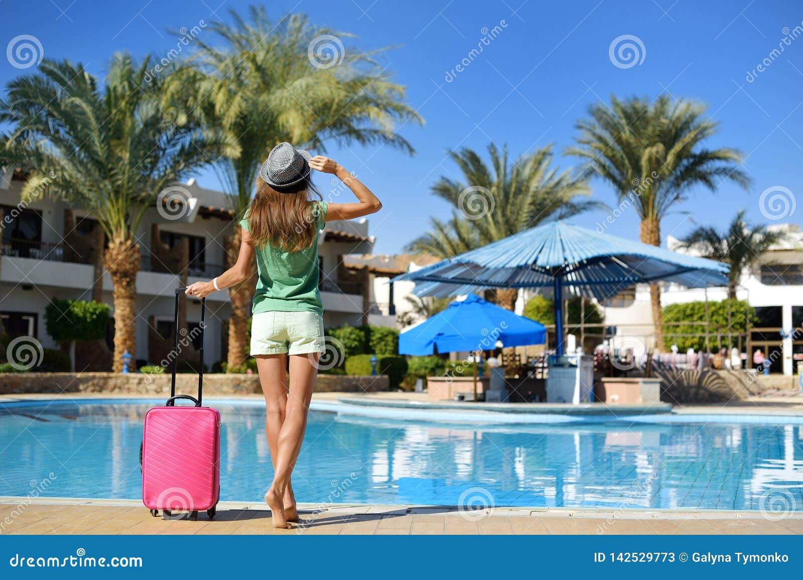 Lopp, sommarferier och semesterbegrepp - härlig kvinna som går nära hotellpölområde med den rosa resväskan
