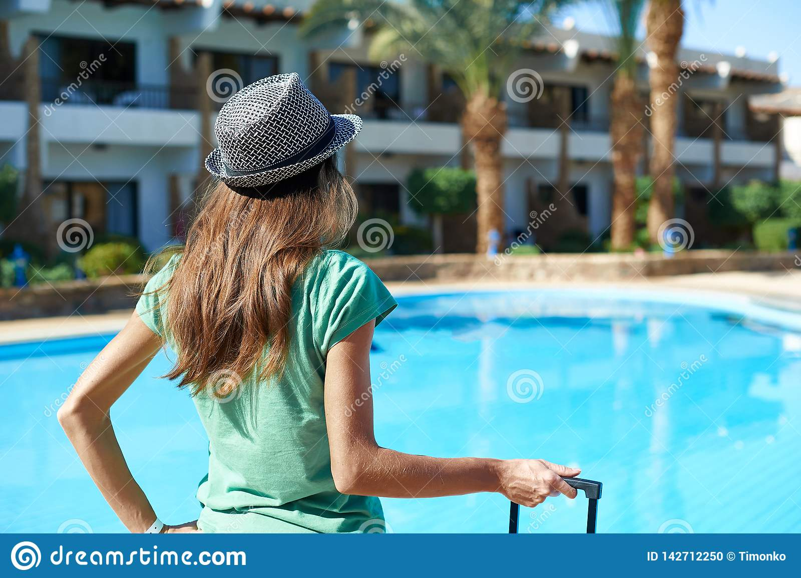 Lopp, sommarferier och semesterbegrepp - härlig kvinna som går nära hotellpölområde med resväskan i Egypten