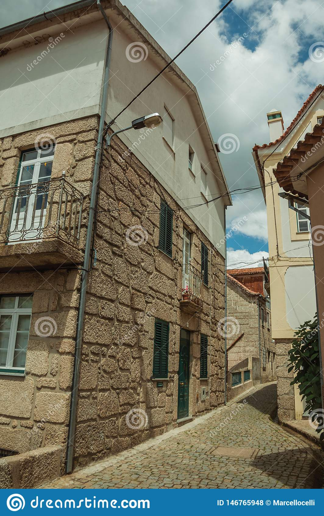 Deserted alley and old two-store house with stone wall