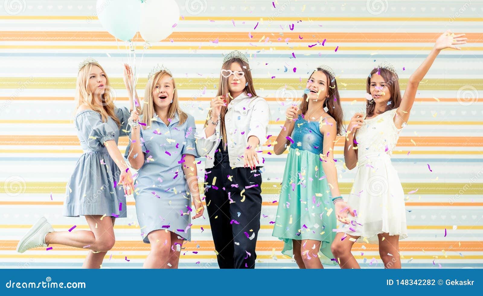 Los adolescentes bastante sonrientes en vestidos alegre aumentaron las manos juntas y corren slappers con las chispas en la fiest