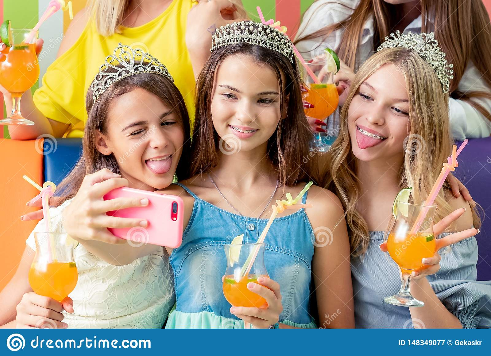 Los adolescentes bastante sonrientes en vestidos y coronas se sientan abrazando juntas sostener las bebidas
