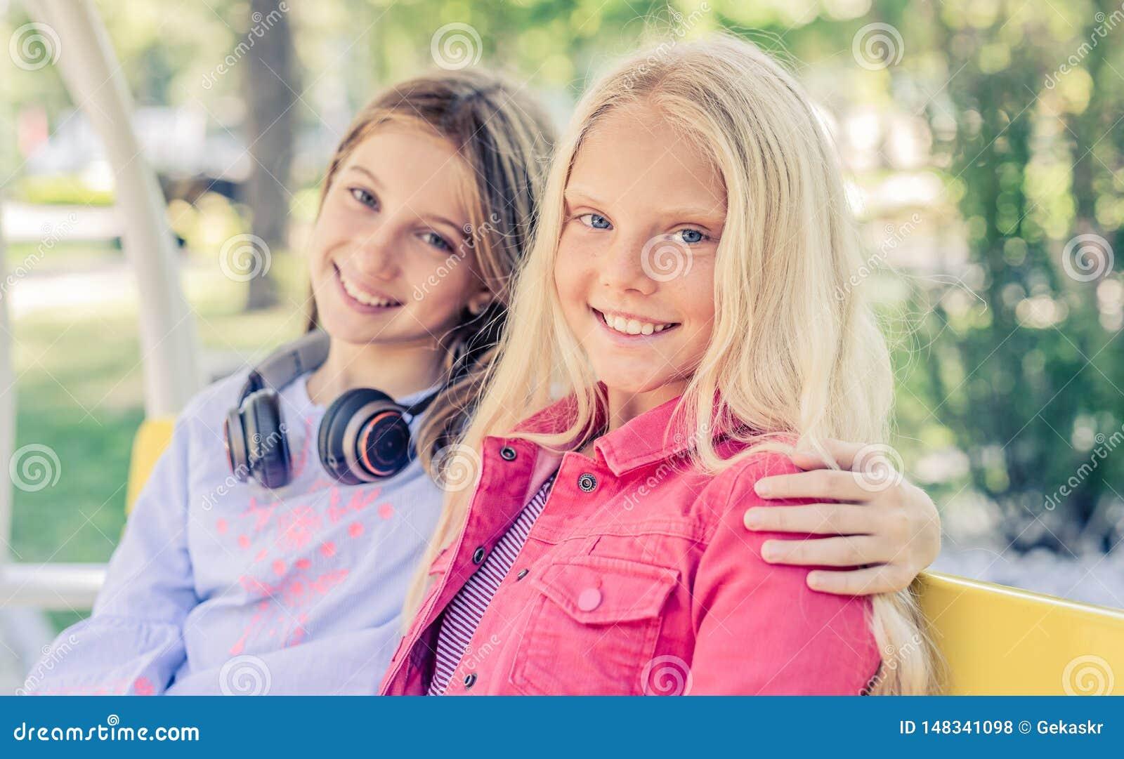 Los adolescentes sonrientes bonitos sientan el abrazo juntos
