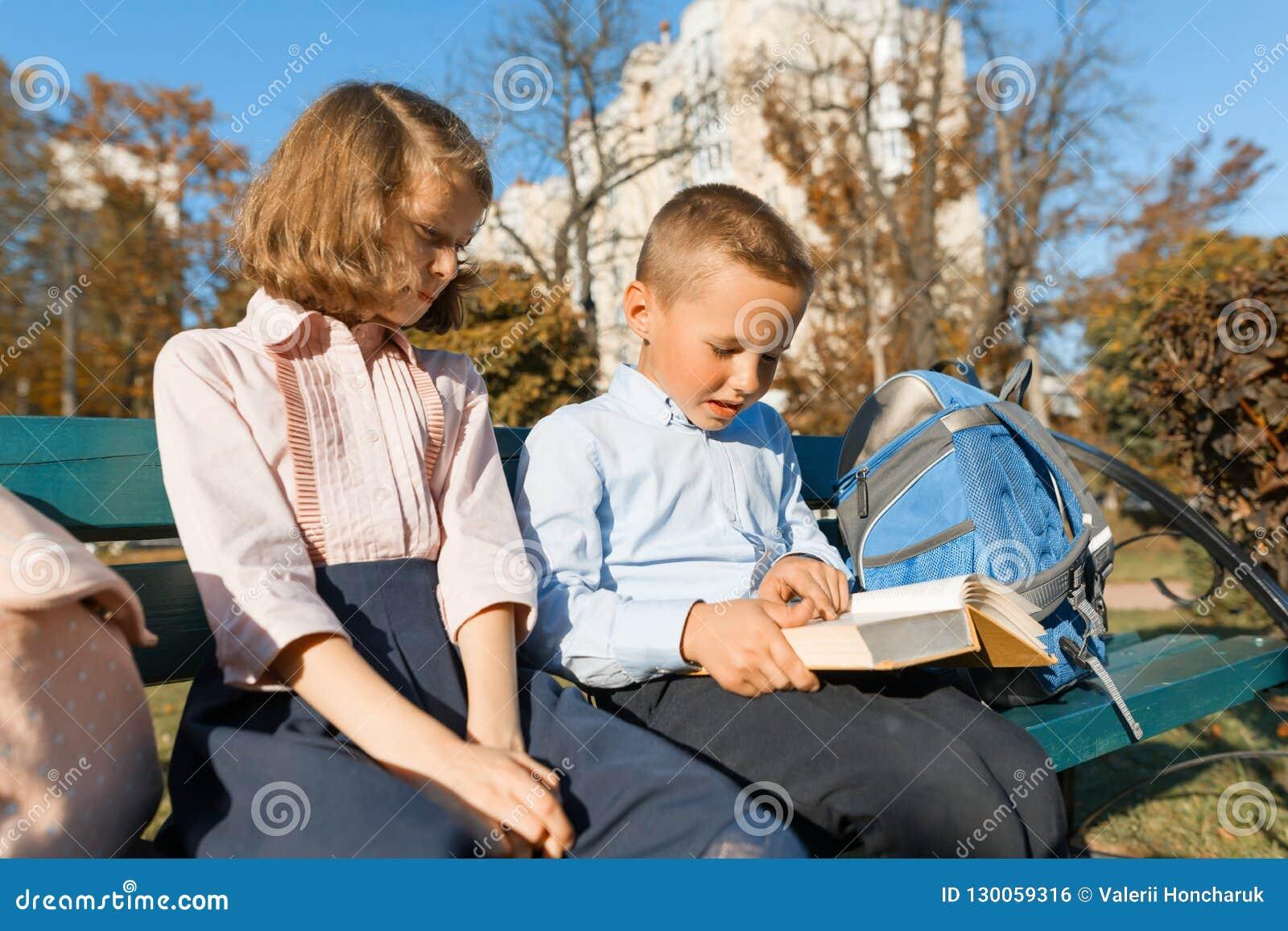 Los alumnos del niño pequeño y de la muchacha leyeron un libro, se sientan en un banco, niños con las mochilas, día soleado brill