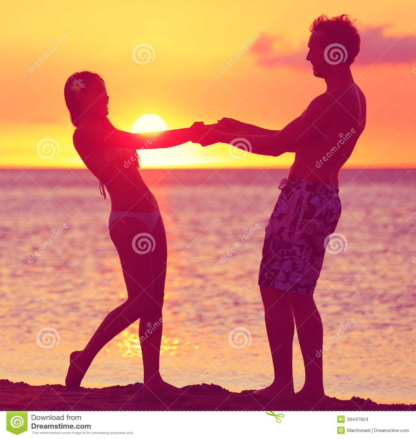 Los amantes juntan tener romance de la diversión en la playa de la puesta del sol