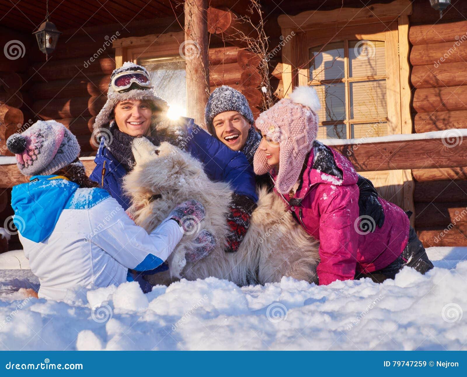 Los amigos alegres con el perro pasan vacaciones de invierno juntas en la cabaña de la montaña