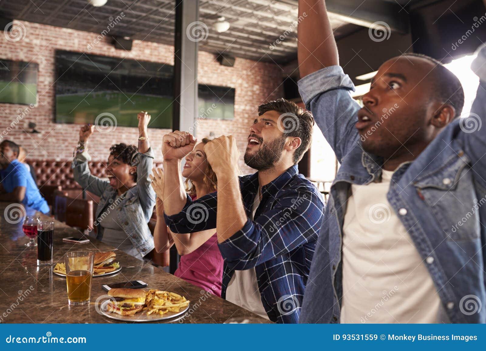 Los amigos en el contador en juego del reloj de la barra de deportes y celebran