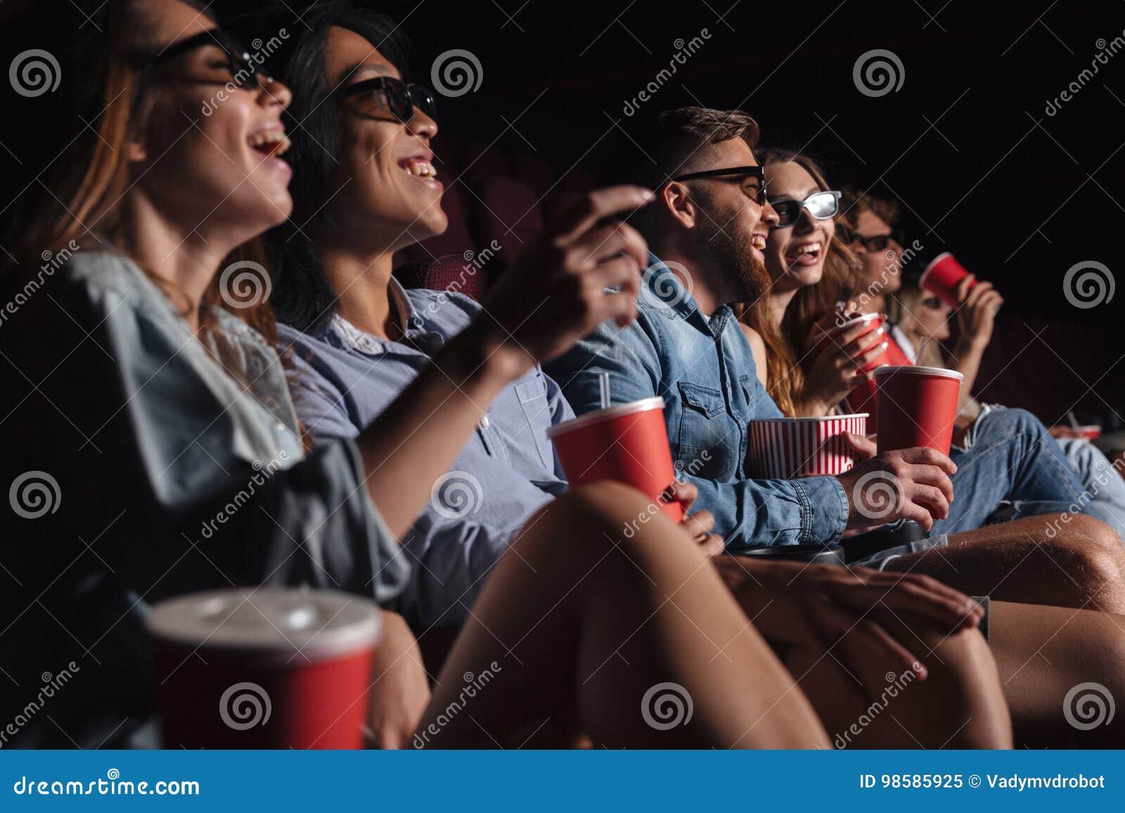 Los amigos felices que se sientan en cine miran la película el comer de las palomitas