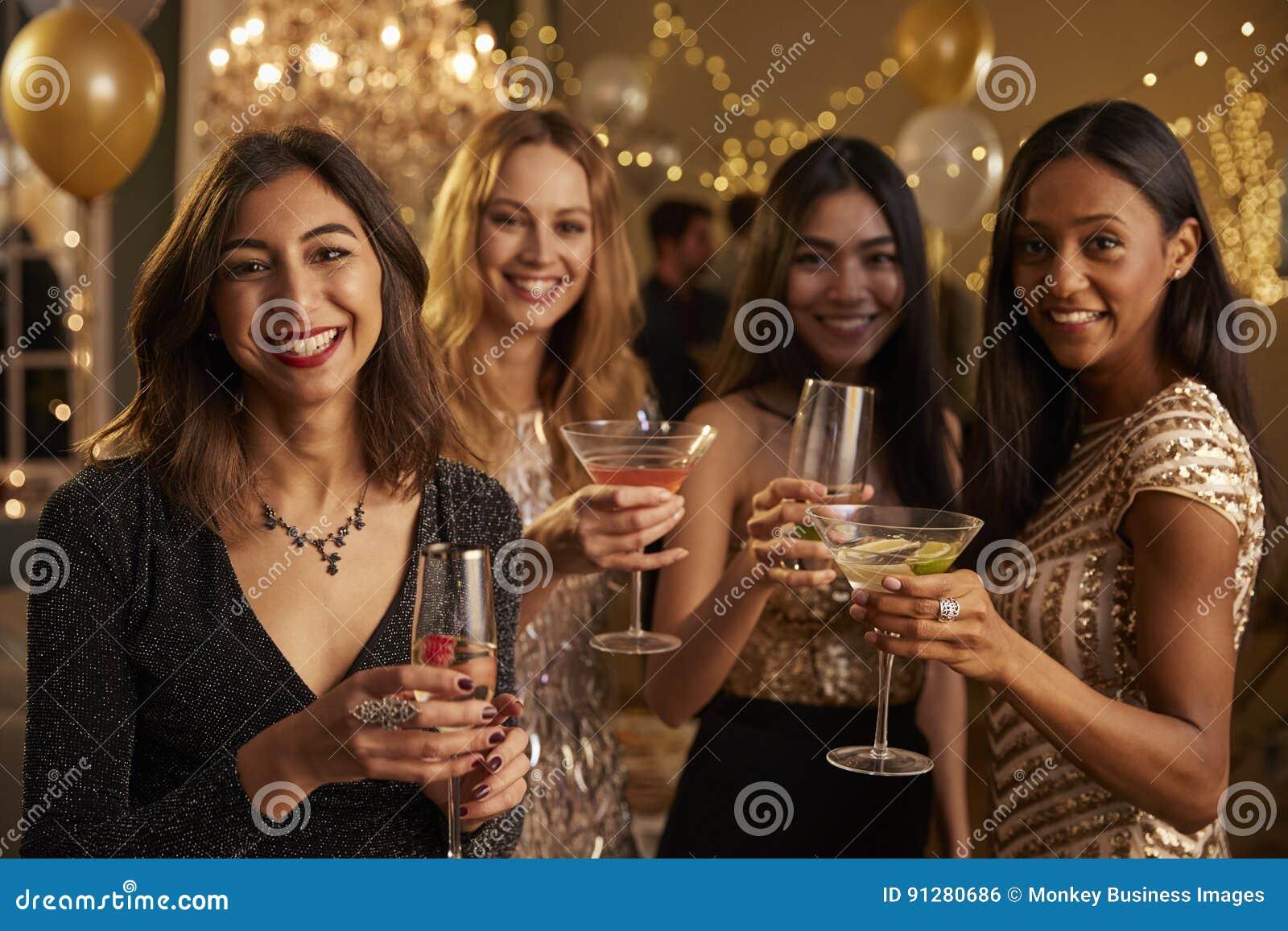 Los amigos femeninos que celebran en el partido hacen la tostada a la cámara