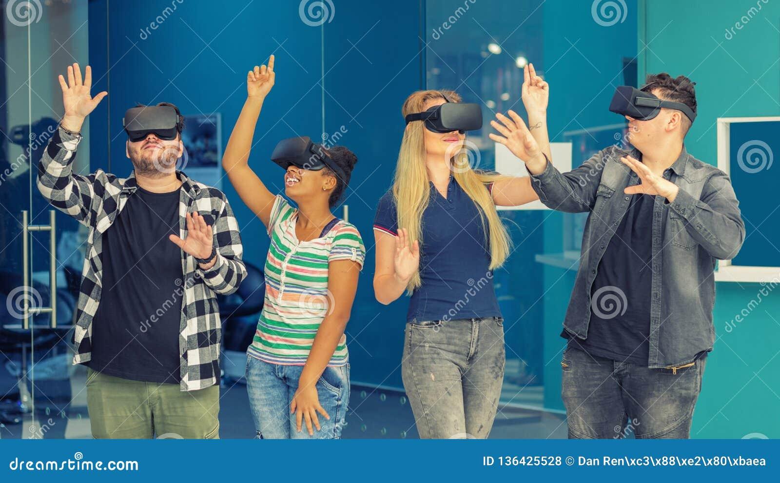Los amigos multirraciales agrupan jugar sobre los vidrios del vr dentro Concepto de la realidad virtual con la gente joven que se