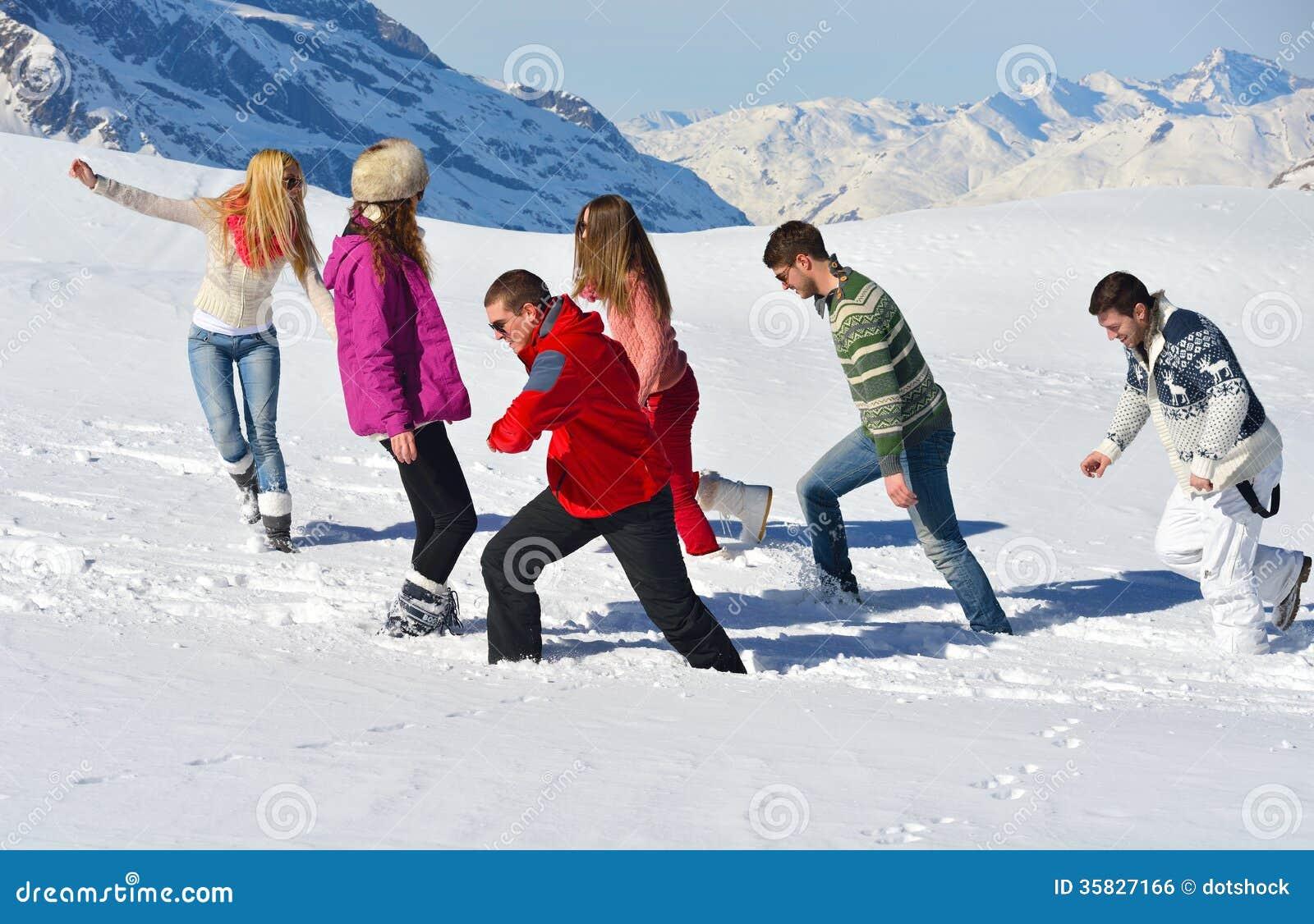 Los amigos se divierten en el invierno en nieve fresca