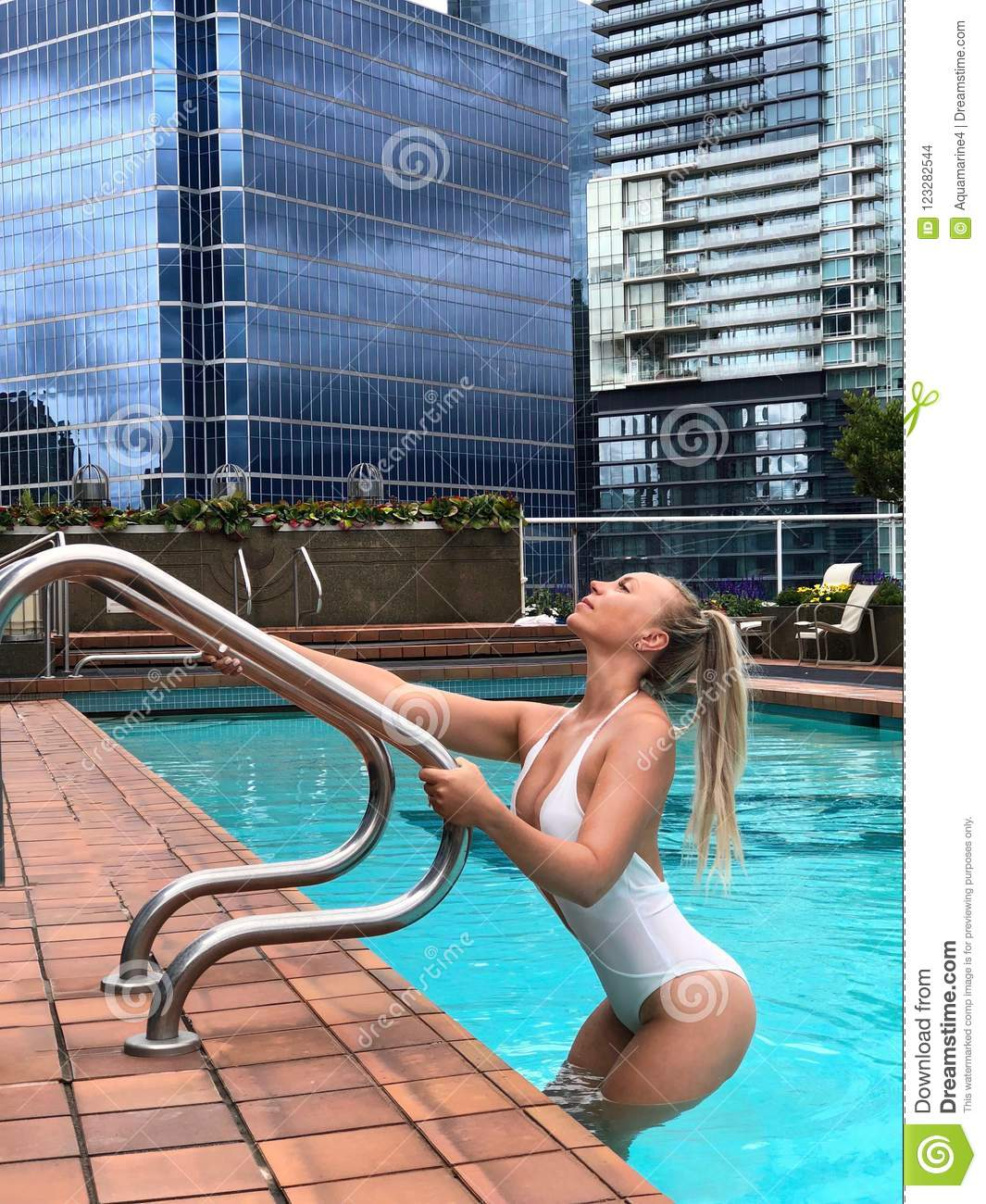 Young beautiful blond woman in swimming pool on the roof top among skyscrapers.