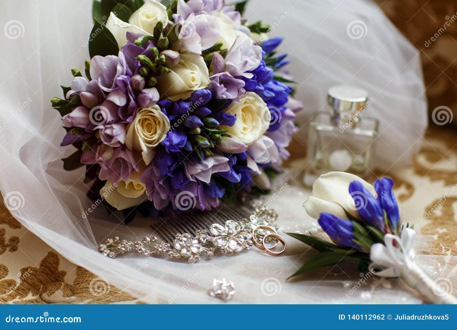 Los anillos de bodas mienten delante del ramo que se casa