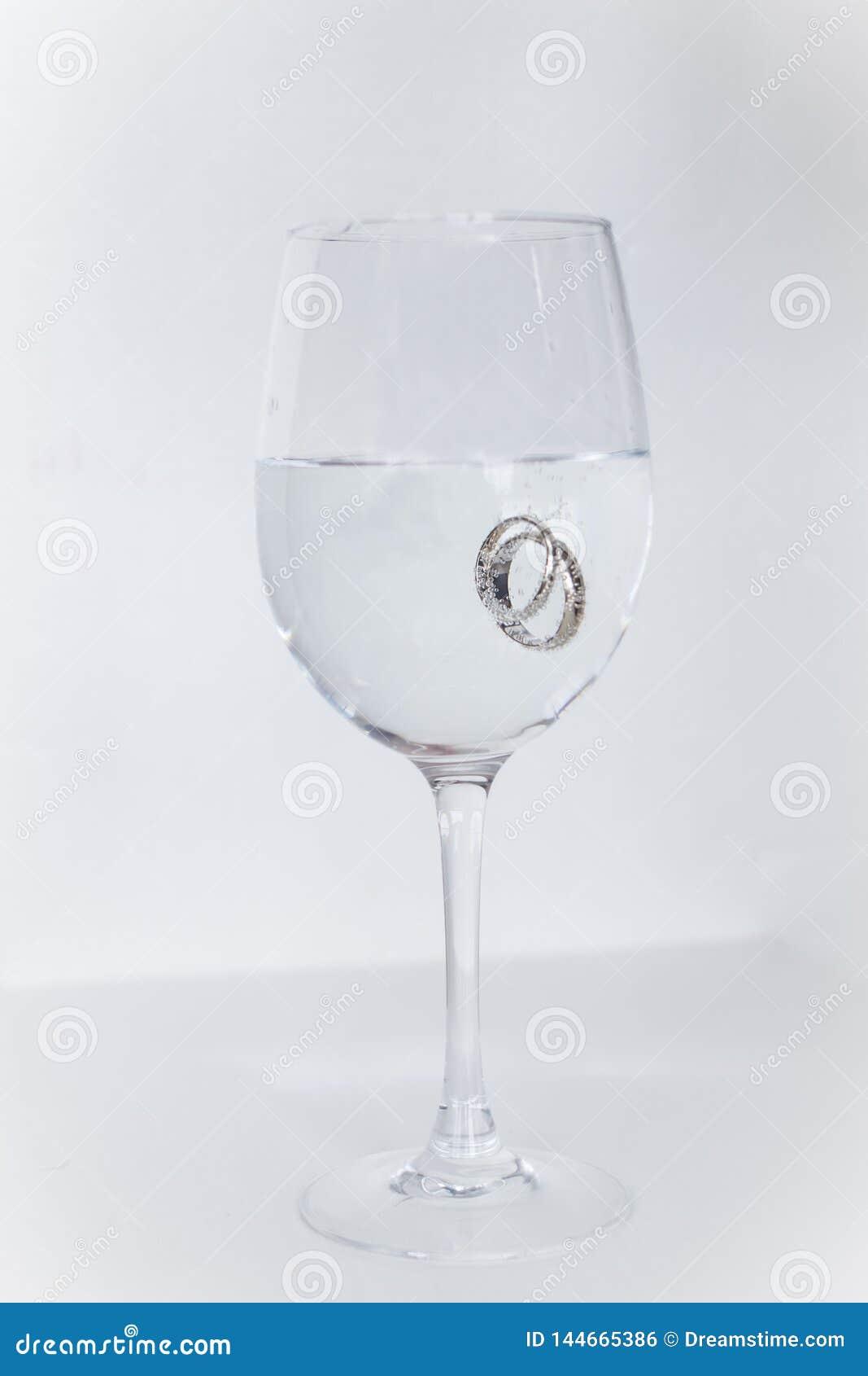 Los anillos de bodas sumergieron en un vidrio llenado de champán