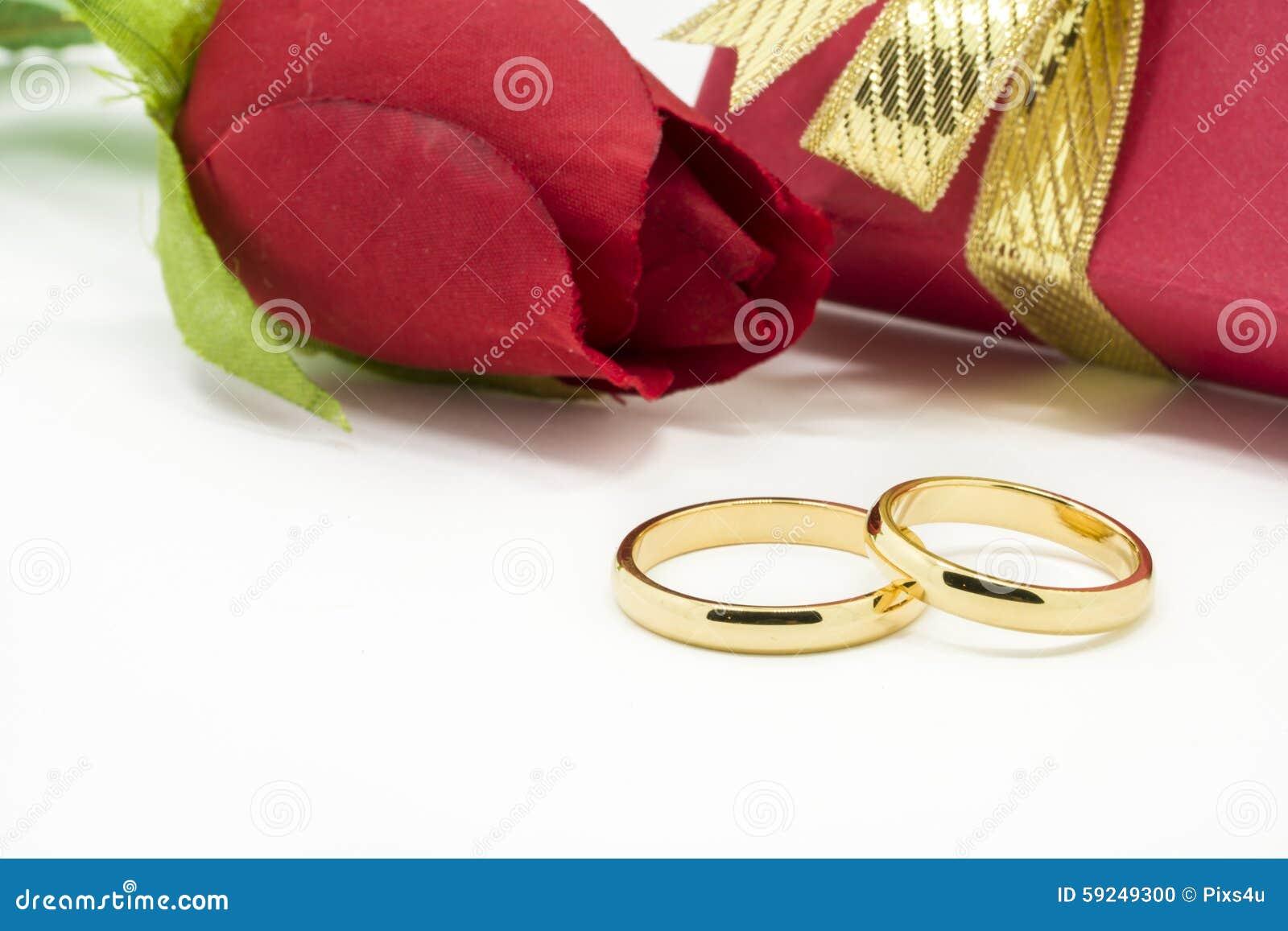 Los anillos de bodas y artificial subieron en el fondo blanco