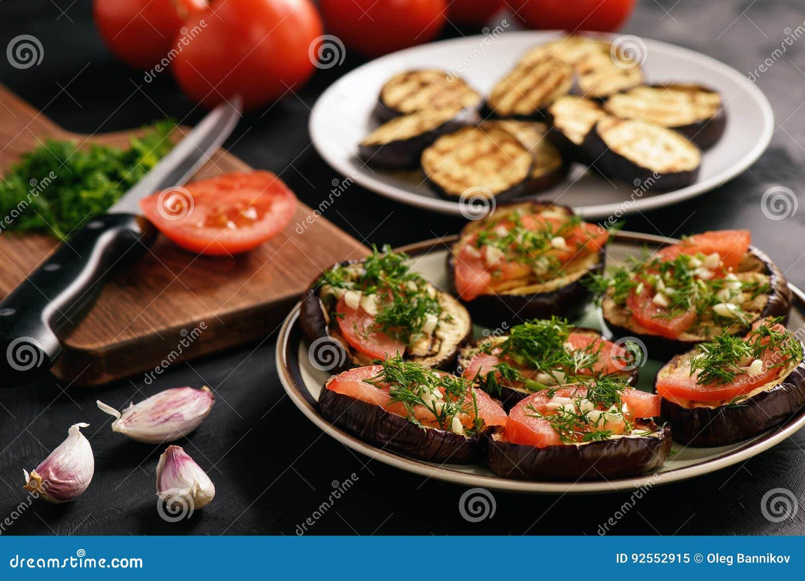 Los aperitivos asaron a la parrilla las berenjenas con los tomates, el ajo y el eneldo