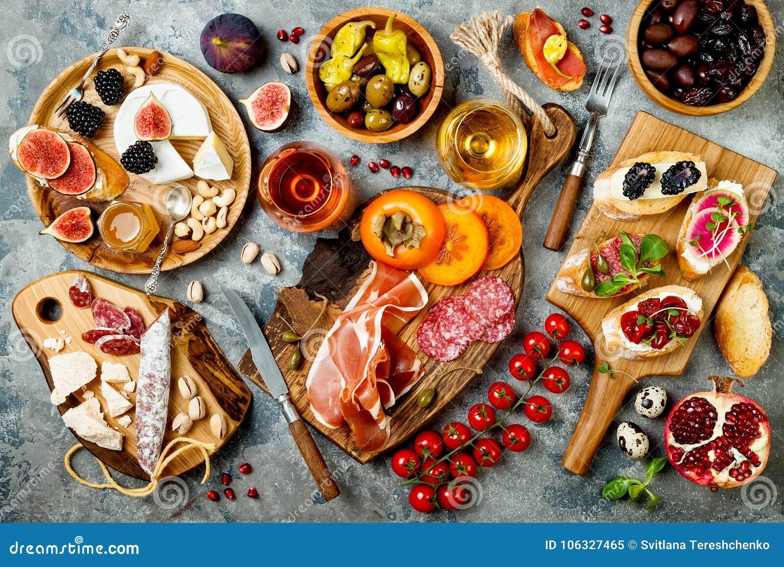 Los aperitivos presentan con bocados y vino italianos de los antipasti en vidrios Brushetta o tapas españoles tradicionales autén