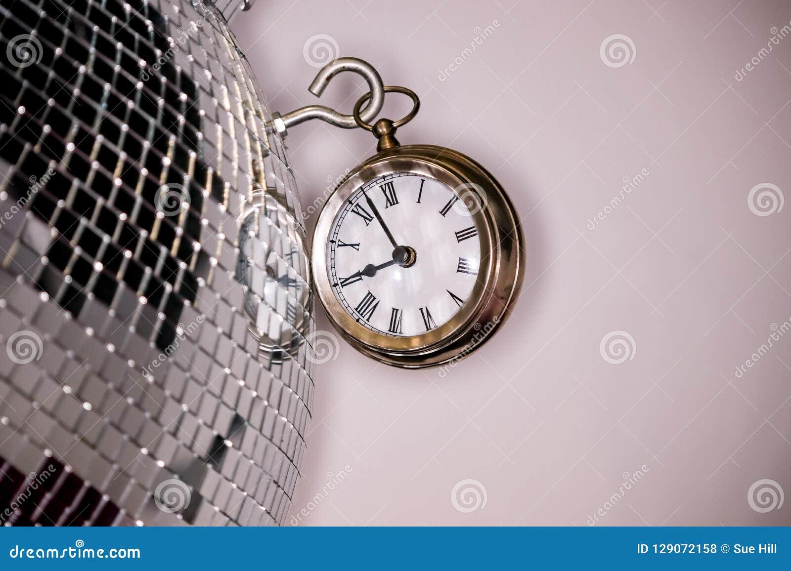 Los Arty tiraron de un reloj grande del reloj de bolsillo del metal al lado de una bola de discoteca de plata
