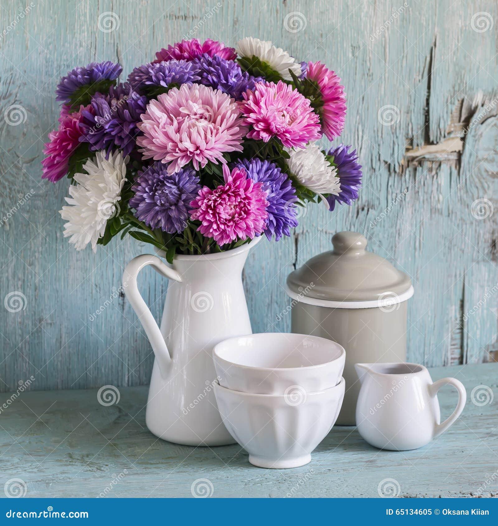 Los asteres de las flores en un blanco esmaltaron la jarra y la loza del vintage - cuenco de cerámica y tarro esmaltado, en un fo
