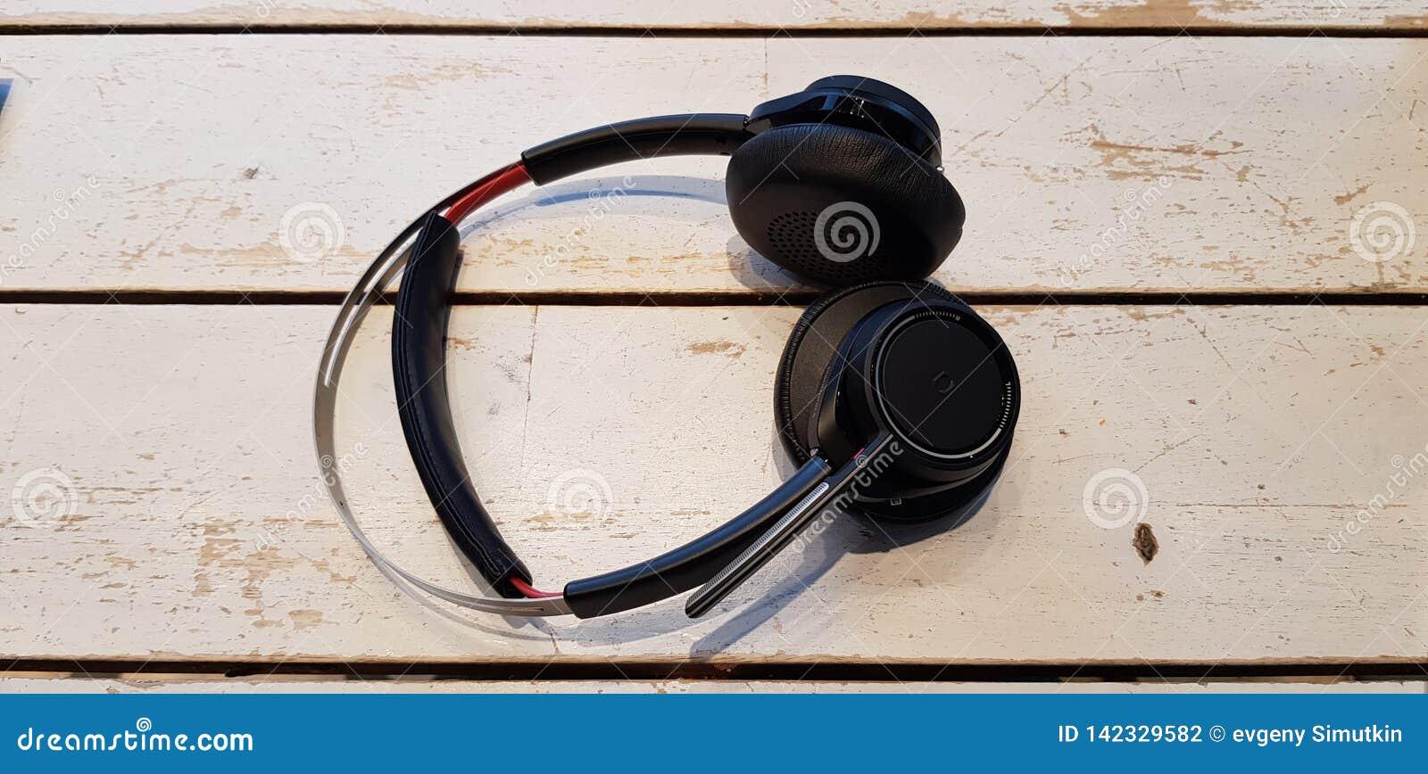 Los auriculares inalámbricos negros ponen en la tabla de madera blanca