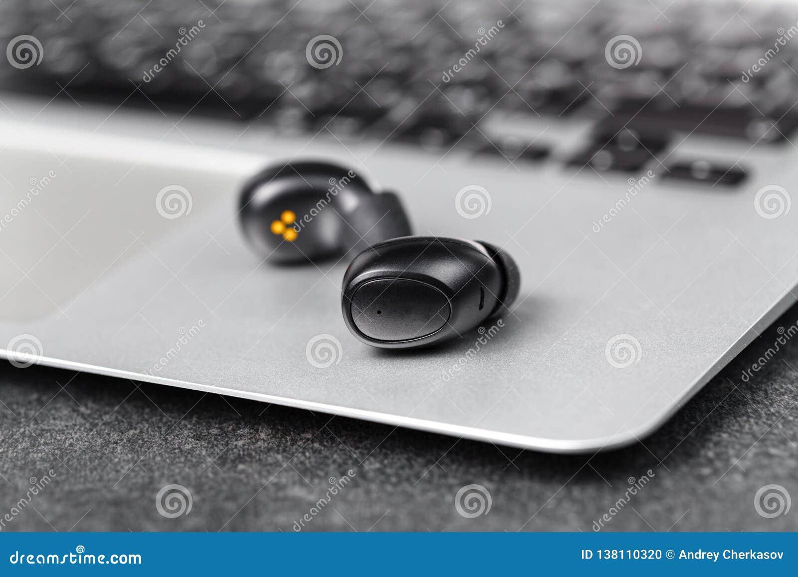 Los auriculares inalámbricos se cierran encima de la opinión sobre piedra negra