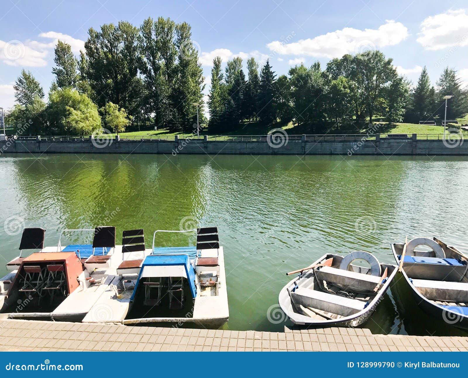 Los barcos y los catamaranes en un lago de la charca en un canal del río con agua florecida verde se amarran en la orilla