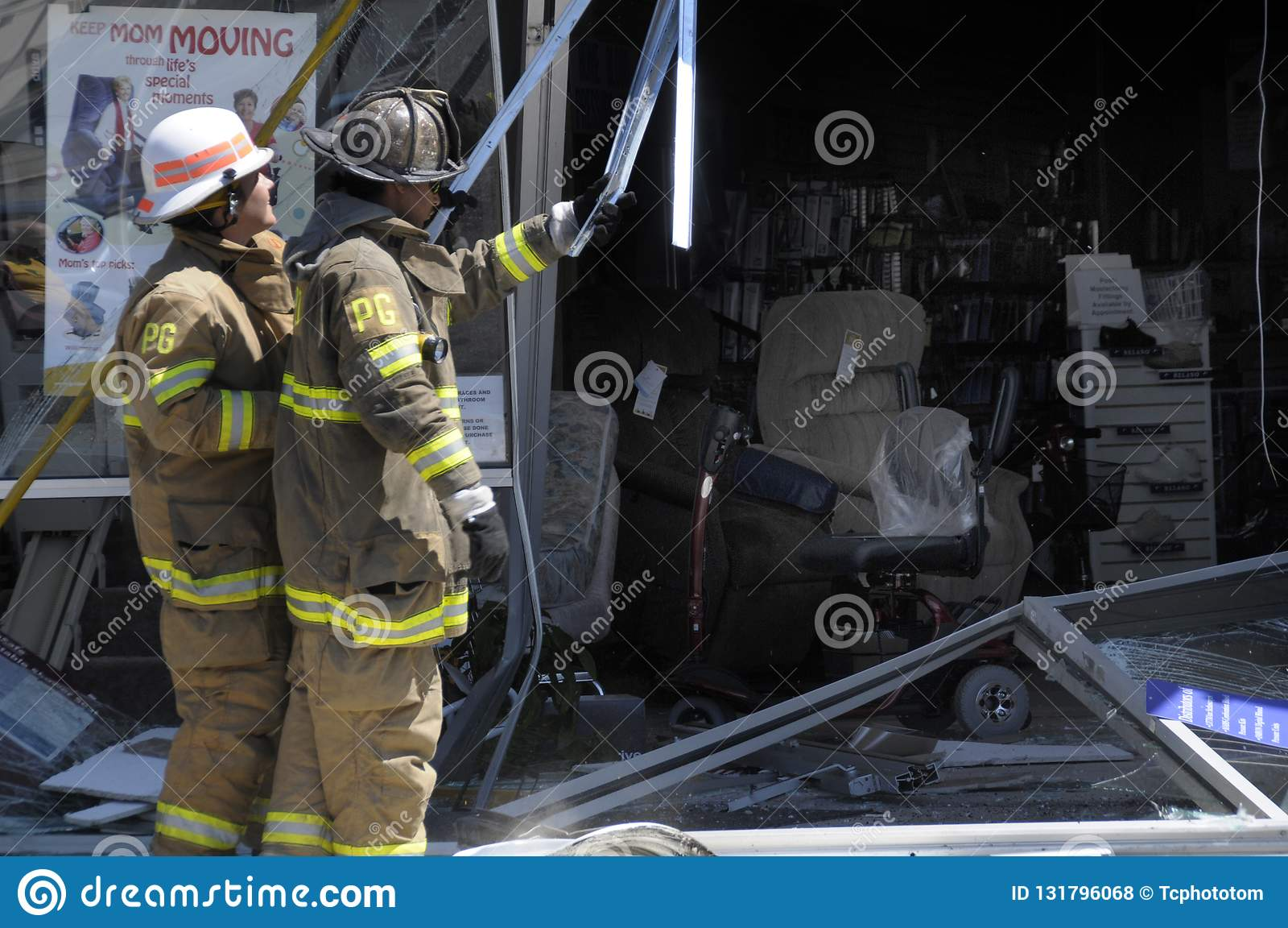 Los bomberos examinan el daño hecho cuando un coche condujo en una tienda del suministro médico en Lahnam, Maryland