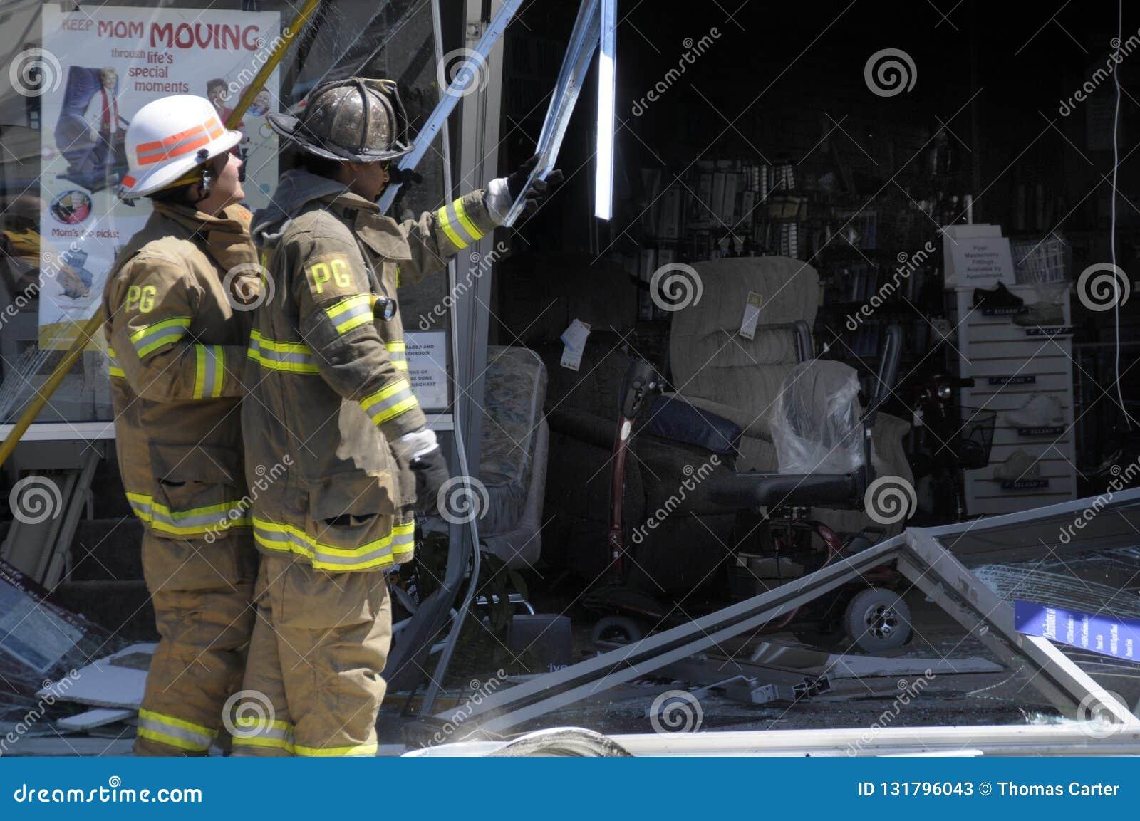 Los bomberos miran el daño hecho cuando un coche condujo en una tienda del suministro médico adentro