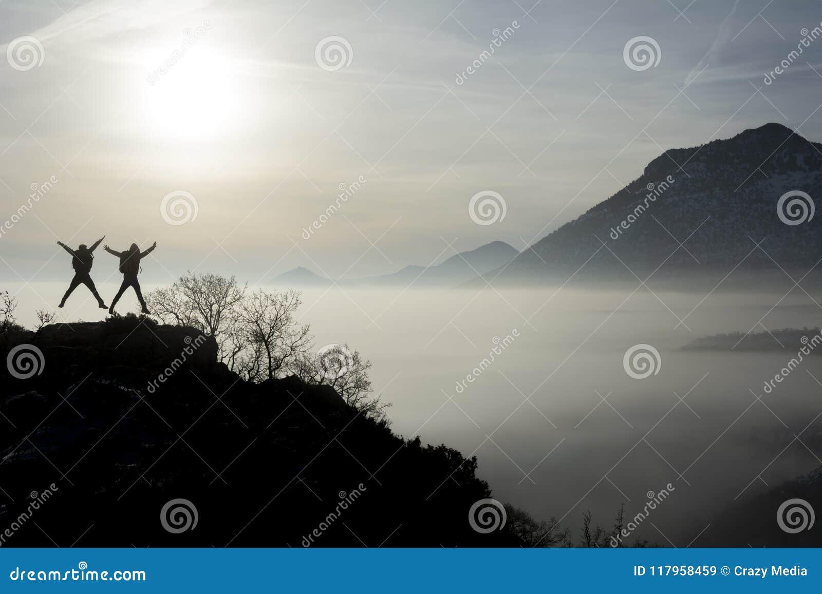 Los caminantes que saltan en la cima de la montaña