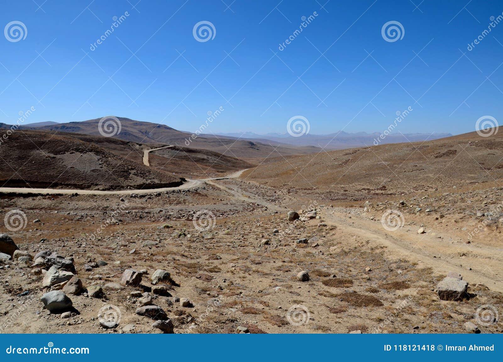 Los caminos bifurcan en los llanos secos y estériles Gilgit-Baltistan Paquistán de Deosai