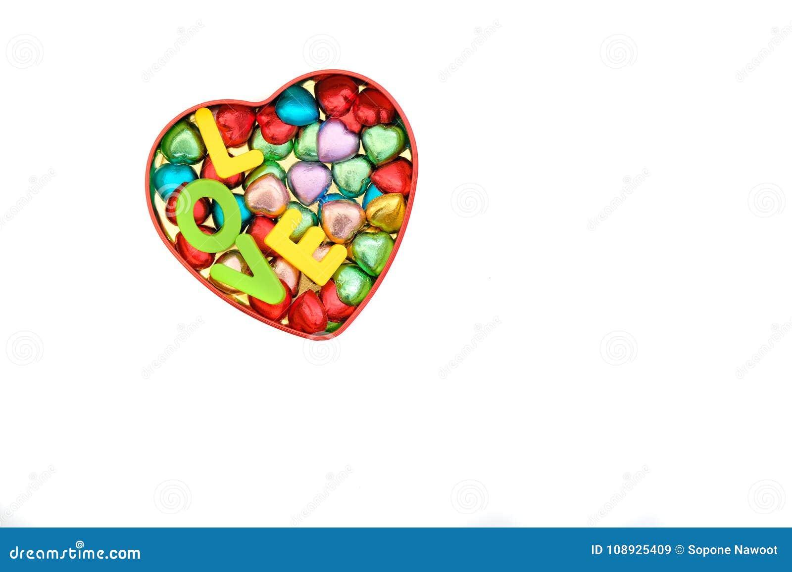 Los caramelos de chocolate en diversos colores en una lata de la corazón-forma encajonan ingenio