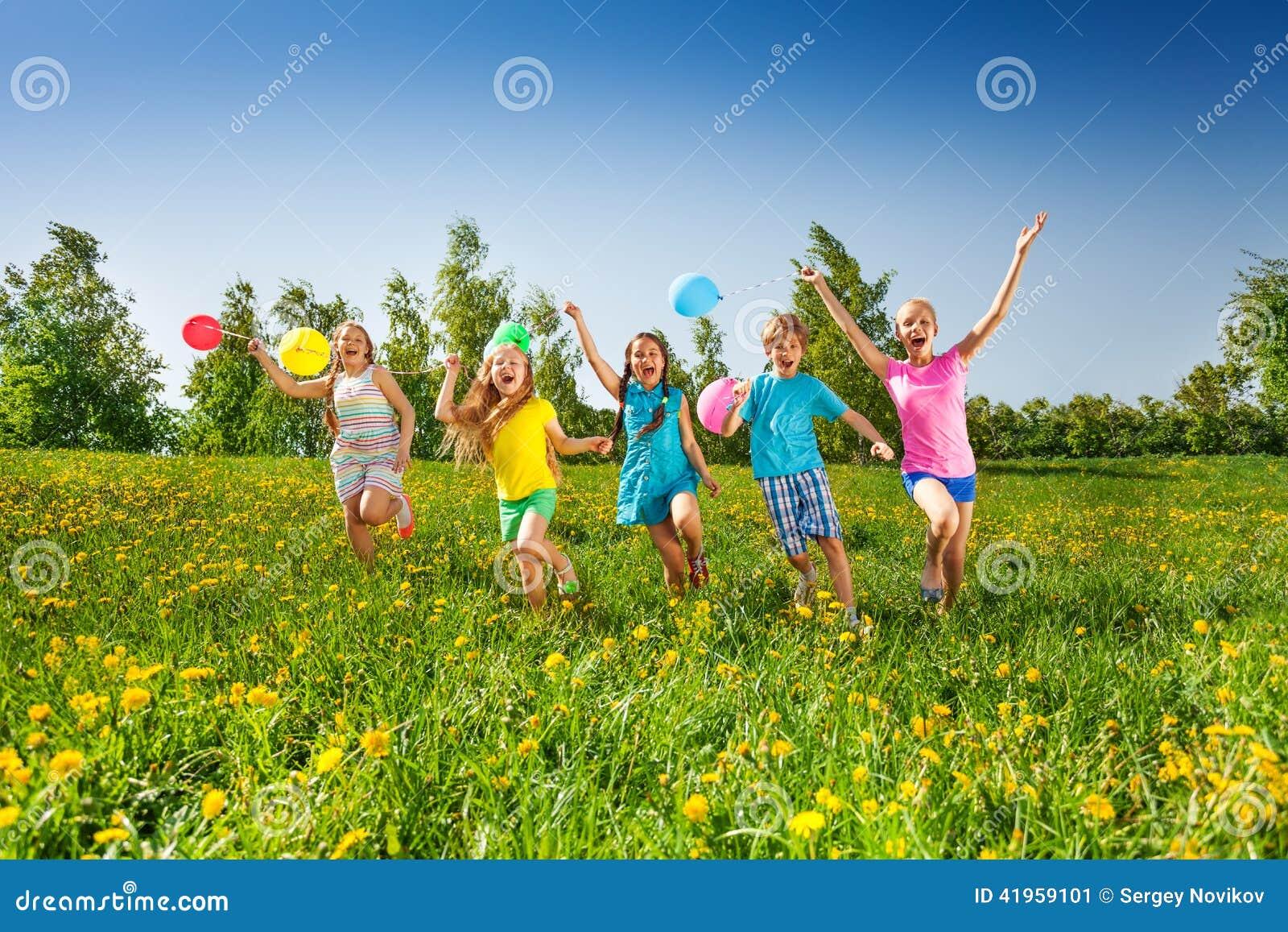Los cinco niños felices con los globos corren en campo