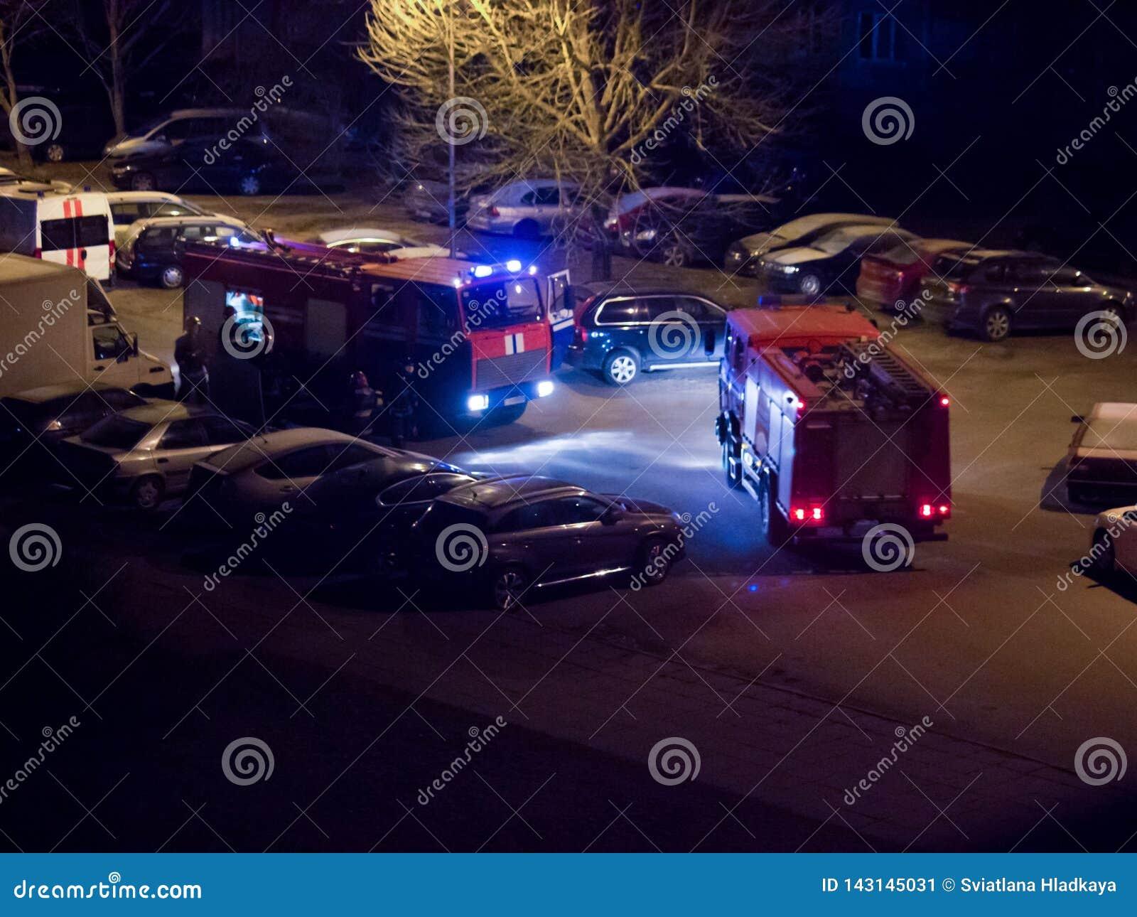 Los coches de bomberos est?n en el camino con las luces que destellan prendido en la noche