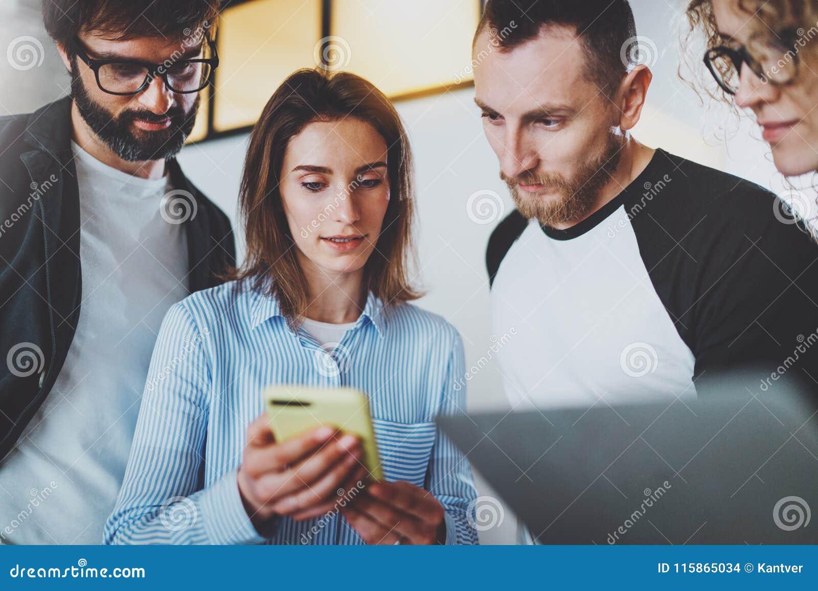 Los compañeros de trabajo combinan el trabajo con los dispositivos móviles en la oficina moderna Concepto de la reunión de negoci
