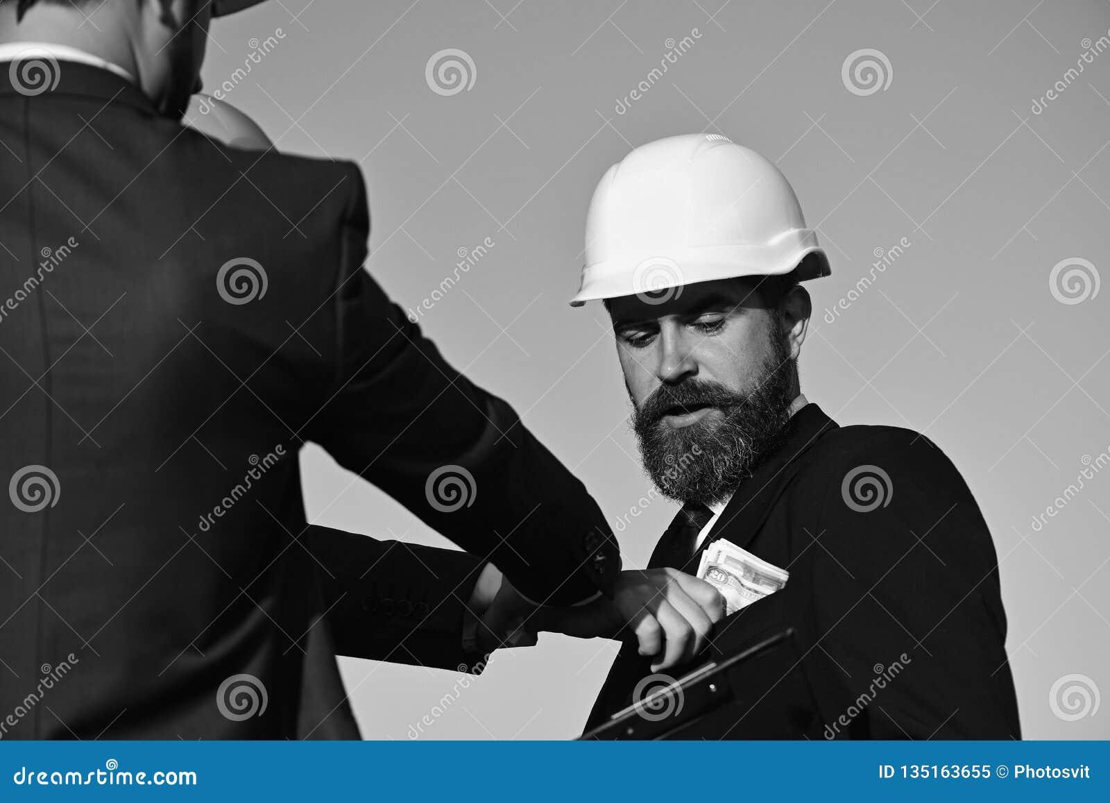 Los constructores hacen negocio Arquitectos con la cara confusa en desgaste formal
