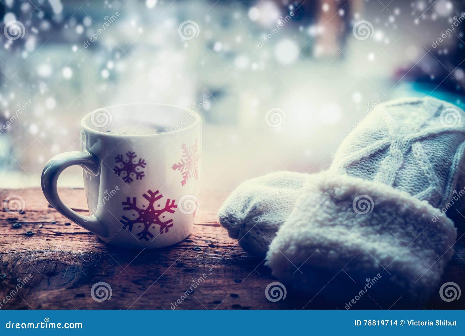 Los copos de nieve asaltan con la bebida caliente y las manoplas que hacen punto en travesaño de la ventana de la helada en la na