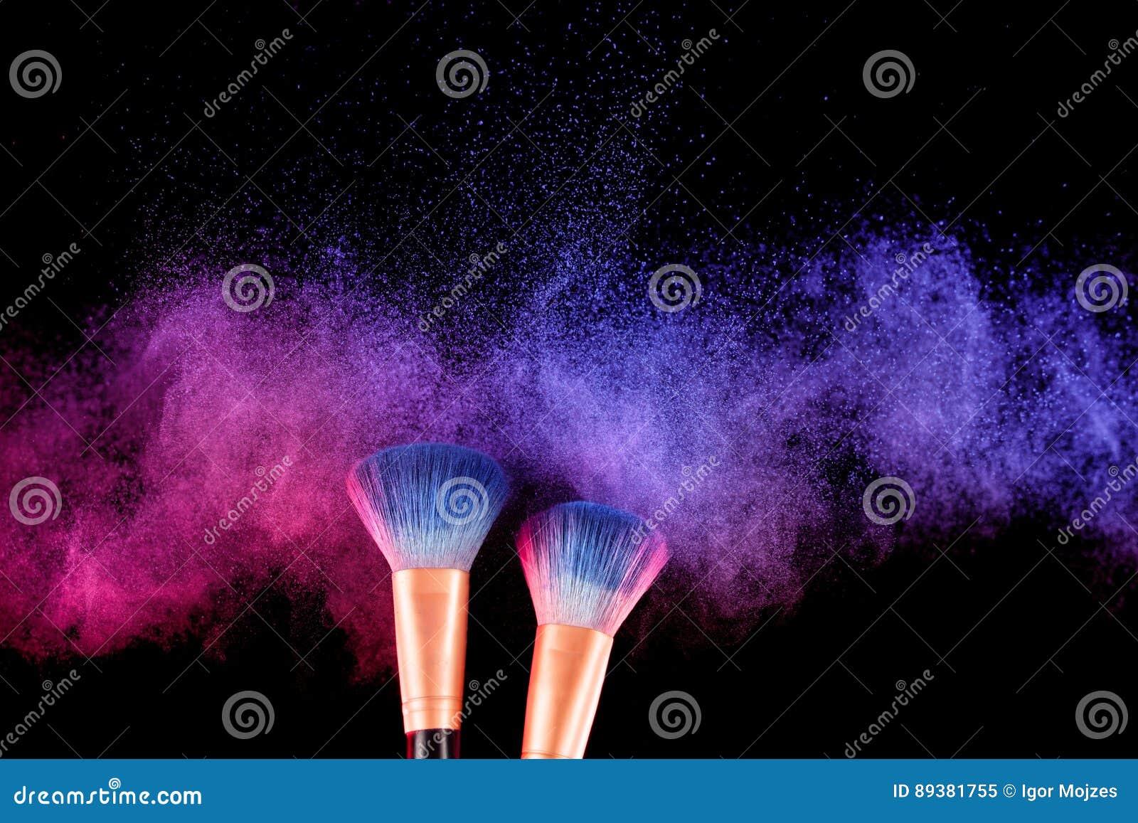 Los cosméticos cepillan y el polvo colorido del maquillaje de la explosión
