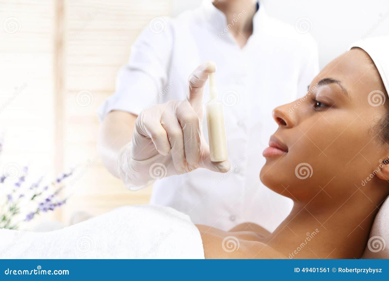 Los cosmetólogos de la mano muestran una ampolla con una preparación cosmética