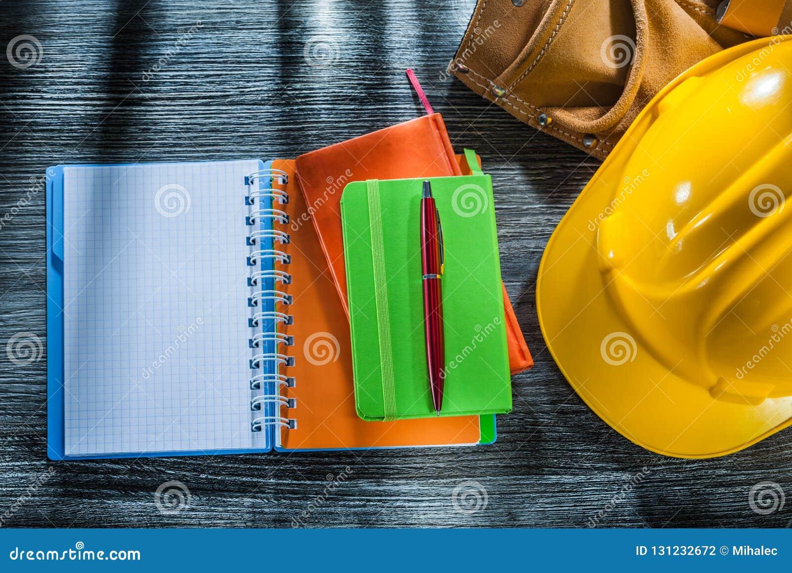 Los cuadernos encierran la correa de cuero de la herramienta de la tapa protectora en el tablero de madera