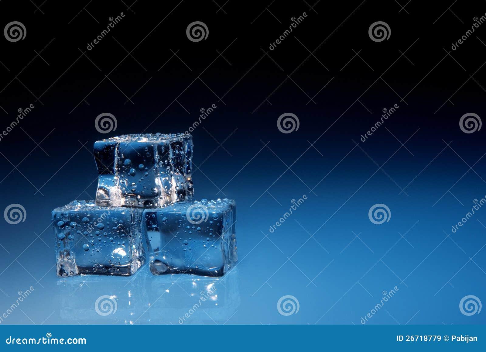 Los cubos de hielo con agua caen el fondo