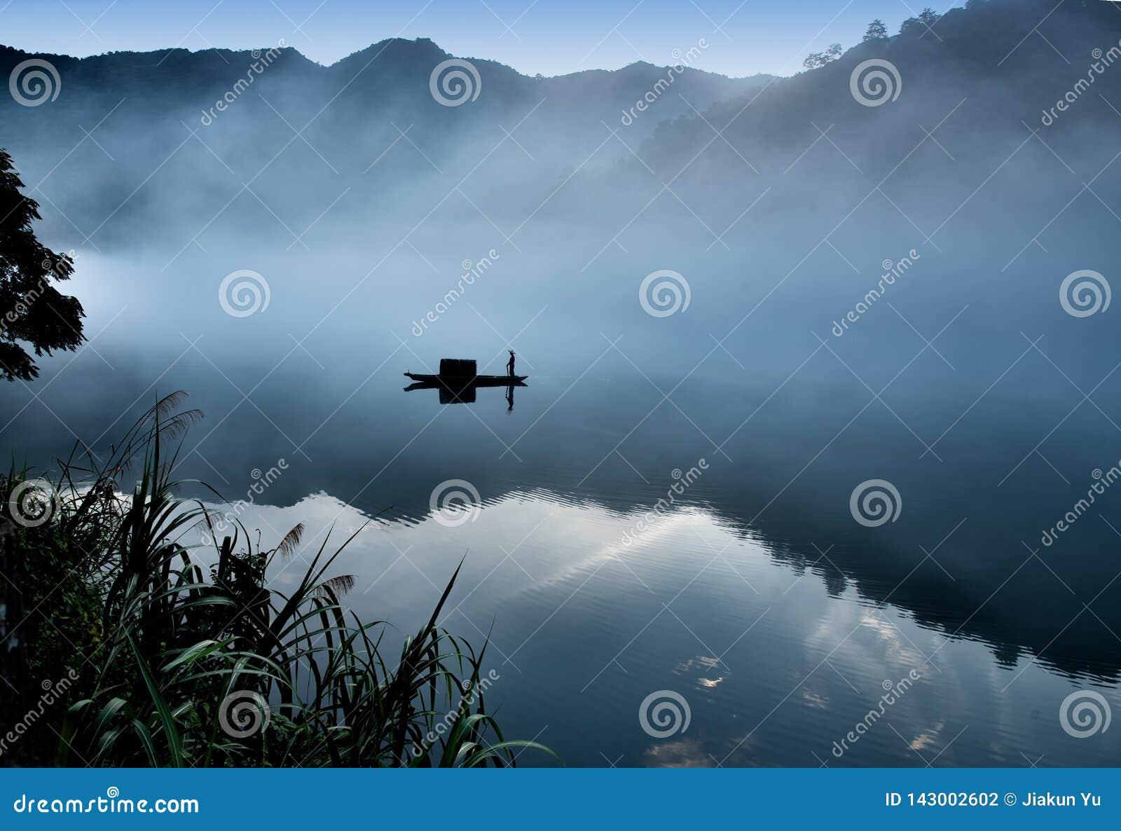 Los cucoloris de un fishman en el barco en la niebla en el río, una reflexión clara en el río tranquilo Tono fr?o