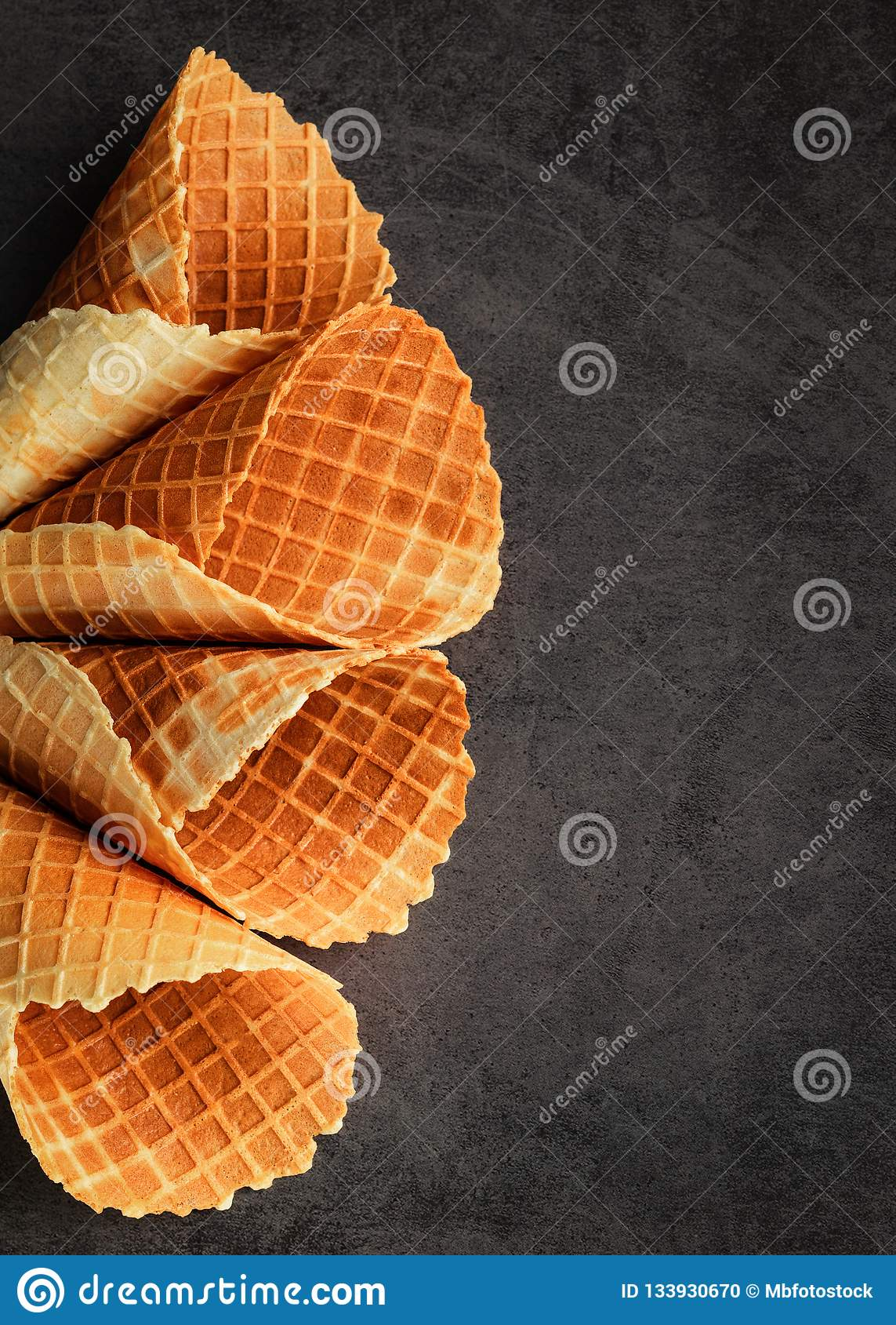 Los cucuruchos o el helado vacíos apilados hechos en casa se enrollan los conos en fondo oscuro