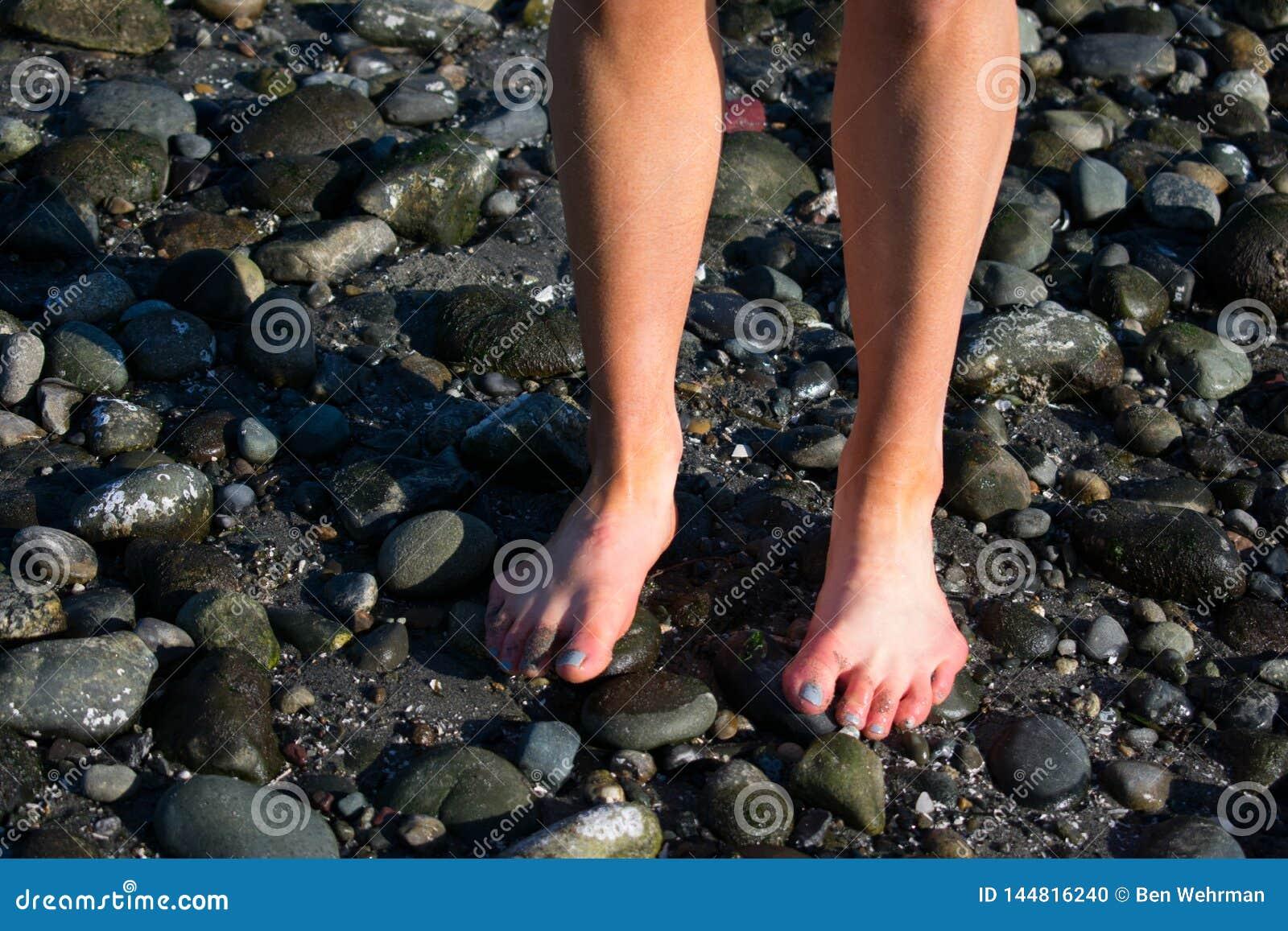 Los dedos del pie de la muchacha en la playa