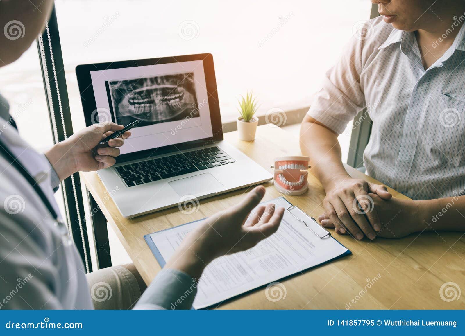 Los dentistas están discutiendo problemas dentales en la imagen de la radiografía del informe en la pantalla del ordenador portát