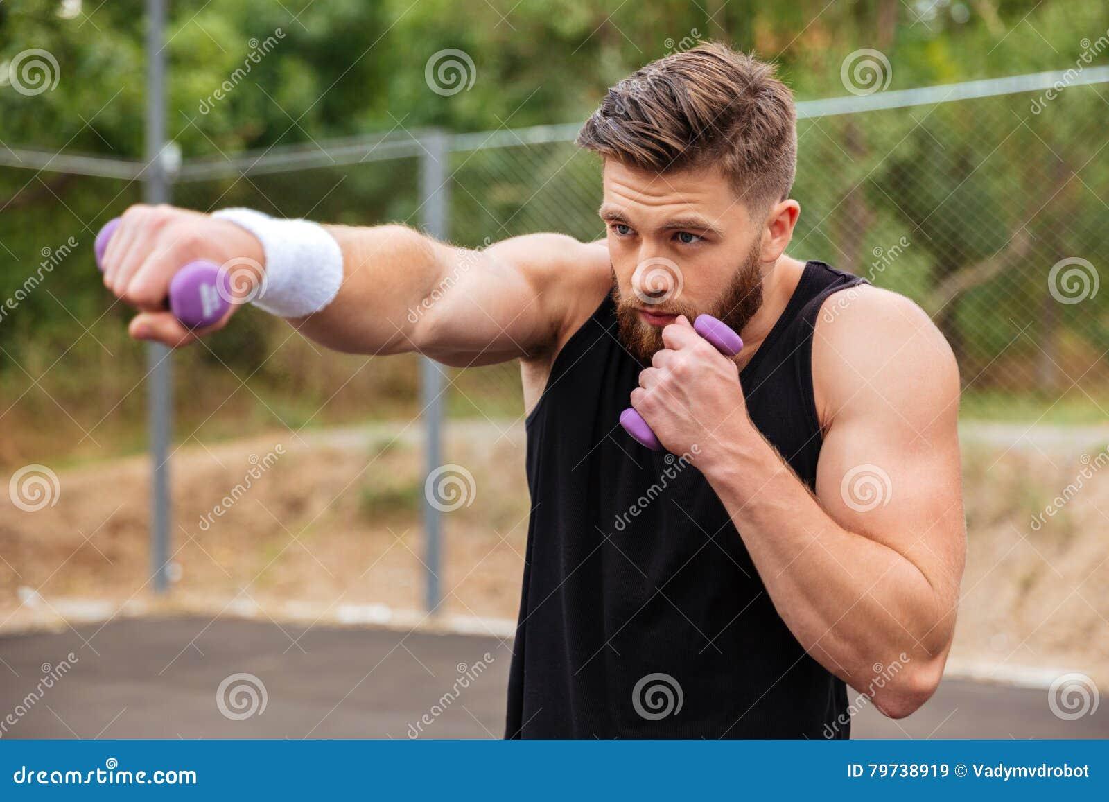 Los deportes barbudos jovenes sirven hacer entrenamiento con pequeñas pesas de gimnasia