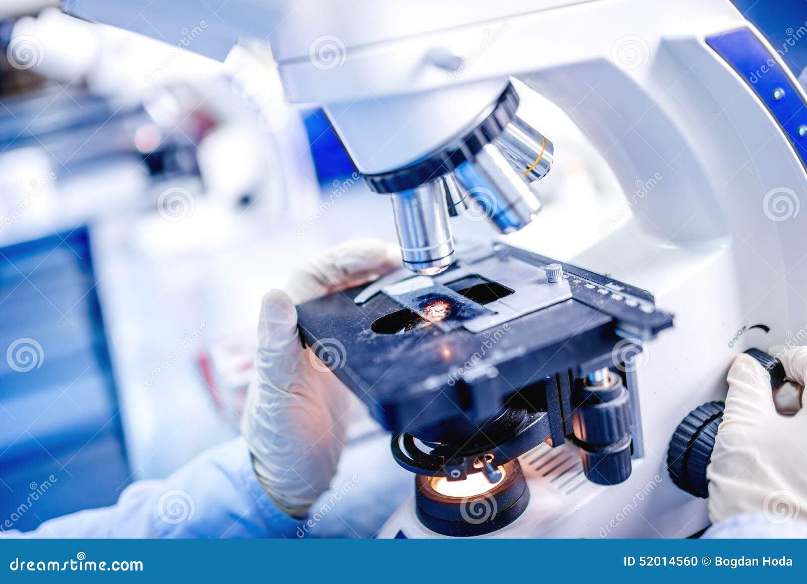 Los detalles del laboratorio médico, manos del científico usando el microscopio para la química prueban muestras