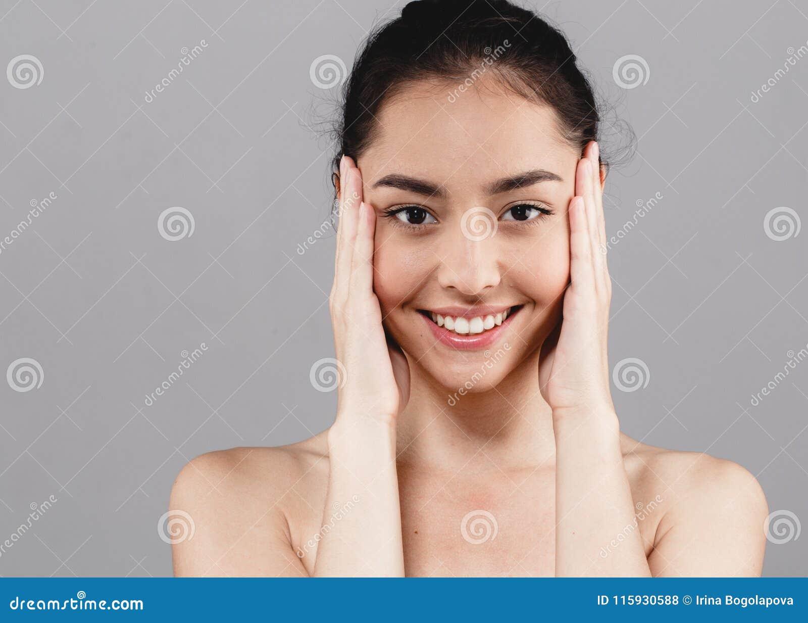 Los dientes hermosos de la cara de la belleza del skincare de la mujer sonríen con handsclo