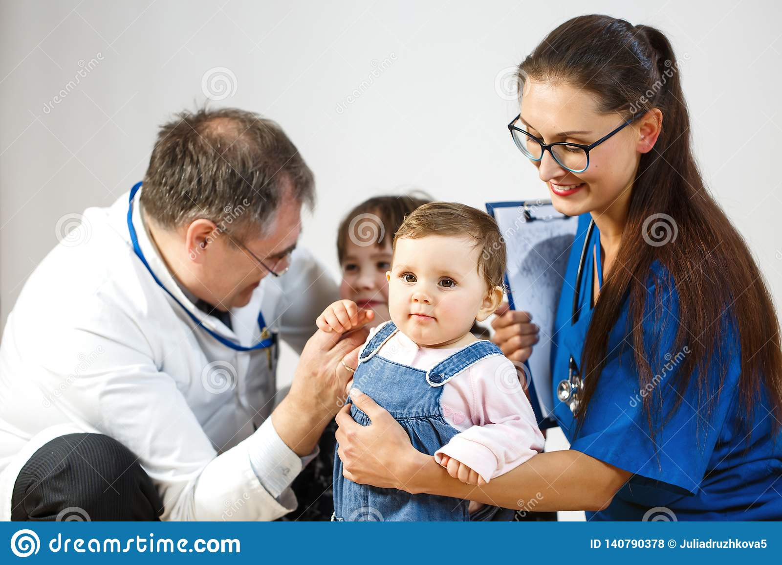 Los doctores examinan a niños, un pequeño niño miran la cámara, sonrisas de un doctor de la mujer joven
